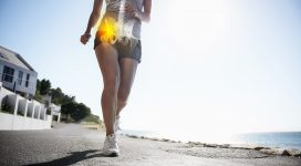 A cropped view of a female jogger on the road experiencing joint inflammation