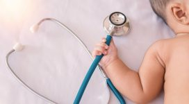 medical instruments stethoscope in hand of newborn baby girl.